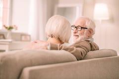 Erfreuter grau-haariger Mann, der nah an seiner Frau sitzt stockfotos