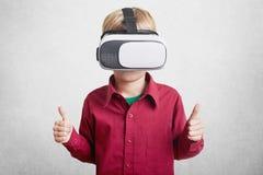 Erfreuter kleiner Junge genießt virtuelle Realität, trägt VR-Kopfhörer, oder Gläser 3D, zeigt okayzeichen, wie, zufrieden stellen Lizenzfreie Stockfotos