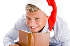 Erfreuter Mann mit Buch und Weihnachtshut Stockbilder