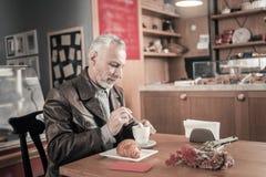 Erfreuter Pensionär, der geht, frühes zu frühstücken stockfotografie