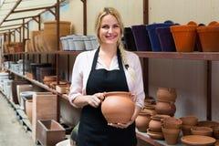 Erfreuter weiblicher Handwerker, der Keramik in der Werkstatt hat lizenzfreie stockbilder