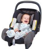 Erfreutes Baby, das im Autositz sitzt Stockfotografie
