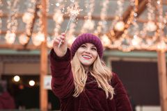 Erfreutes blondes Mädchen kleidete in der stilvollen Kleidung an und hielt das Glühen Stockfoto