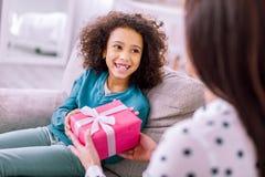 Erfreutes brunette Kind, das zu Hause glücklich ist stockbild
