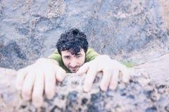 Erfreutes Gesicht des Mannes kletternd über Felsen-Leiste Lizenzfreie Stockbilder
