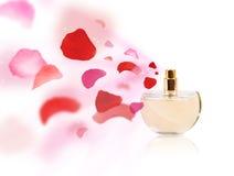 Erfume bottle spraying rose petals. Perfume bottle spraying colorful rose petals stock photography