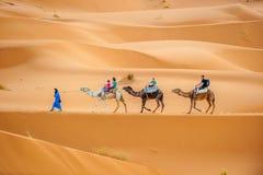 ERG CHEBBY, MAROKKO - April, 12, 2013: Toeristen die kamelen berijden Stock Afbeeldingen