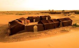 Typical camping in the ERG desert in Morocco. Erg Morocco A classic camp for tourists made up of clay and straw houses covered with traditional curtains .Desert Royalty Free Stock Photography