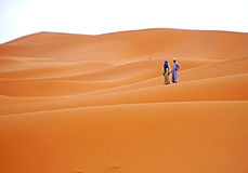Waiting for dawn in the ERG desert in Morocco. Erg Morocco Two tourists on the dunes awaiting the lights of the early morning of dawnn Desert Erg Chebbi in Royalty Free Stock Image