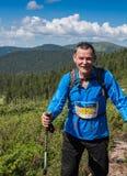 ERGAKI,俄罗斯- 2017年8月05日:一位未知的男性运动员通过山,一个参加者在TRAILANNING跑 免版税库存照片