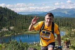 ERGAKI,俄罗斯- 2017年8月05日:一位未知的男性运动员通过山,一个参加者在TRAILANNING跑 库存照片