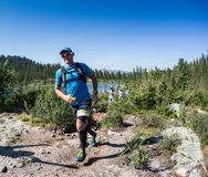 ERGAKI,俄罗斯- 2017年8月05日:一位未知的男性运动员通过山,一个参加者在TRAILANNING跑 免版税图库摄影