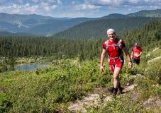 ERGAKI,俄罗斯- 2017年8月05日:几位运动员通过山,落后SKAYRANFEST的参加者跑 免版税图库摄影
