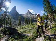 ERGAKI, RÚSSIA - 5 DE AGOSTO DE 2017: Diversos atletas correm através das montanhas, participantes que arrastam o SKAYRANFEST Imagem de Stock Royalty Free