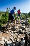 ERGAKI, RÚSSIA - 5 DE AGOSTO DE 2017: Diversos atletas correm através das montanhas, participantes que arrastam o SKAYRANFEST Foto de Stock Royalty Free
