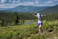 ERGAKI ROSJA, SIERPIEŃ, - 05 2017: Niewiadomy dziewczyny sportsmenki bieg przez gór, uczestnik w trailrunning Fotografia Stock