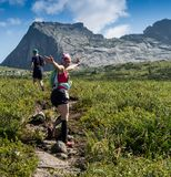 ERGAKI, RUSSIA - AUGUST 05 2017: Several athletes run through the mountains, participants trailing the SKAYRANFEST Royalty Free Stock Images