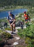 ERGAKI RYSSLAND - AUGUSTI 05 2017: Flera idrottsman nen kör till och med bergen, deltagare som skuggar SKAYRANFESTEN Royaltyfria Foton