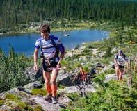 ERGAKI RYSSLAND - AUGUSTI 05 2017: Flera idrottsman nen kör till och med bergen, deltagare som skuggar SKAYRANFESTEN Royaltyfria Bilder