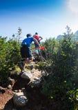 ERGAKI RYSSLAND - AUGUSTI 05 2017: Flera idrottsman nen kör till och med bergen, deltagare som skuggar SKAYRANFESTEN Arkivfoto