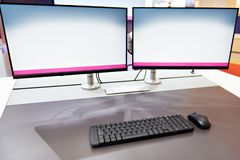 Ergonomic workplace with keyboard and monitors. Concept stock images