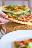 Ergreifung einer Scheibe der Pizza Stockbild