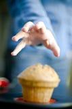 Ergreifung eines Muffins Stockfoto