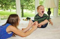 Ergreifungsfuß des Mädchens, Junge, der gekitzeltes Lachen ist lizenzfreies stockfoto