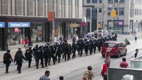 Erhöhte Ansicht der Polizeilinie marschierend durch Stadtzentrum stock video