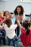 Erhöhte Ansicht von Säuglingsschulkindern in einem Kreis im Klassenzimmer, das ihrem lächelnden weiblichen Lehrer hohe fives, ver stockfotos