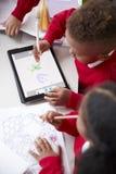 Erhöhte Ansicht von zwei Kindergartenschulkindern, die an einem Schreibtisch in einer Klassenzimmerzeichnung mit einem Tablet-Com stockfoto