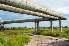 Erhöhter Abschnitt der Rohrleitungen über dem Schotterweg Stockbilder
