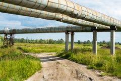 Erhöhter Abschnitt der Rohrleitungen über dem Schotterweg Lizenzfreie Stockfotografie