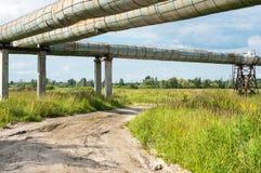 Erhöhter Abschnitt der Rohrleitungen über dem Schotterweg Lizenzfreies Stockfoto