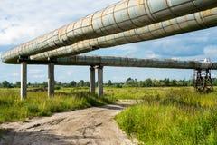 Erhöhter Abschnitt der Rohrleitungen über dem Schotterweg Lizenzfreie Stockfotos