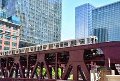 Erhöhter Zug, der die Stadt mit den Skylinen von Wolkenkratzern hinter es durchläuft Lizenzfreie Stockfotografie