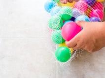 Erhalten des schmutzigen Plastikballs in einer Nettotasche Stockfotos