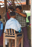 Erhalten eines Haarschnitts am Wochenmarkt Stockbilder