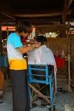 Erhalten eines Haarschnitts am Wochenmarkt Stockbild