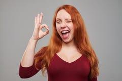 Erheiterte Frau, die okay Geste und das Blinzeln macht Lizenzfreies Stockbild