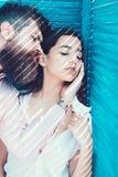 Erhitzen Sie Konzept Verbinden Sie das Kühlen nahe Jalousie, Streifen des Sonnenlichts und Schatten auf Gesichtern Mädchen in auf lizenzfreie stockbilder
