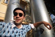 Erholung des jungen Mannes und Rauchzigarette Stockfoto
