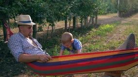 Erholung im Freien, Kind rüttelt seinen Vater in der Hängematte zwischen Baumreihen am Apfelgarten stock video footage