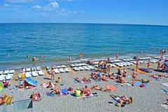 Erholungsort, Leute auf dem allgemeinen Pebble Beach nahe Schwarzem Meer in Alushta, Ukraine, Stockbild