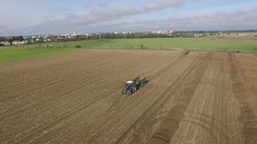 Aerial bulldog tractor with trailer loader driving down an field. Bulldog tractor with trailer loader driving down an field  4k Aerial stock video