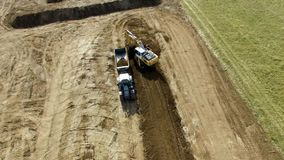 Aerial bulldog tractor with trailer loader driving down an field. Bulldog tractor with trailer loader driving down an field  4k Aerial stock video footage