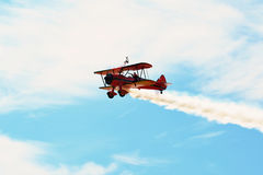 Erinnerungs-Airshow Rotes Stearman-Doppeldeckerfliegen in Richtung zur Kamera beim Schleppen des Rauches in der Ausstellung stockfoto