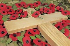Erinnerungstagesmohnblumen, die ein hölzernes Kreuz umgeben stockfotografie