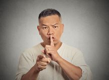 Erious man asking to keep quiet pointing finger at you camera Royalty Free Stock Photo