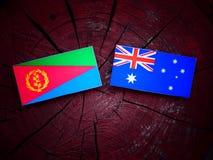 Eritrean σημαία με την αυστραλιανή σημαία σε ένα κολόβωμα δέντρων που απομονώνεται Στοκ Εικόνες